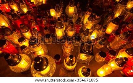 Bunch of glass candles in the dark cemetery - stock photo