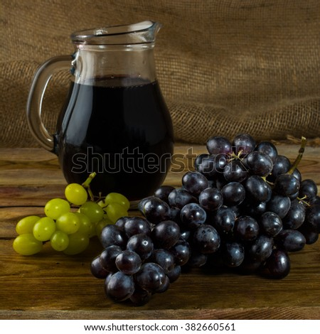 Bunch of grapes and a Wine jug  on a dark wooden background. Bunch of grapes. Cluster grapes.  Bunch grapes. Grapes. Grape. Glass of wine. Glass wine. Grape vine - stock photo