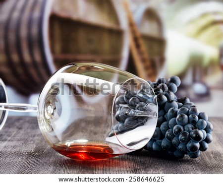 Bunch of grapes and glass of red wine lying on a black wooden table on the background of the wine cellar with barrels. - stock photo