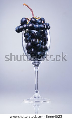 Bunch of Grapes in translucent blue wine glass - stock photo