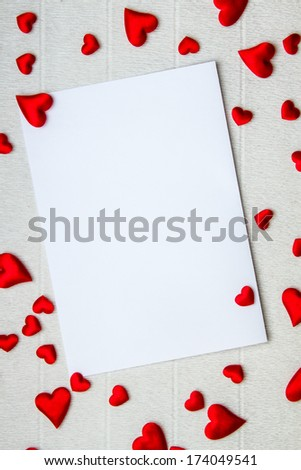 Bunch of hearts of various sizes scattered around an empty postcard - stock photo