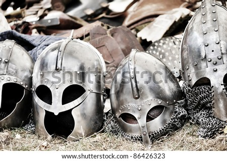 Bunch of helmets and armors after the big battle - stock photo