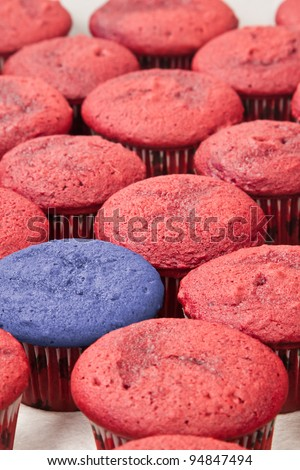bunch of home made red velvet cupcakes in rows with one of them in blue coloring - stock photo