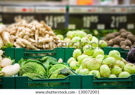 Bunch of kohlrabi and savoy cabbages on boxes in supermarket - stock photo