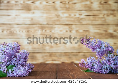 Bunch of lilac flowers on brown wood table with empty space for text