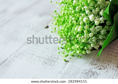 Bunch of lilies of the valley on the white  rustic wooden floor. Horizontal background - stock photo