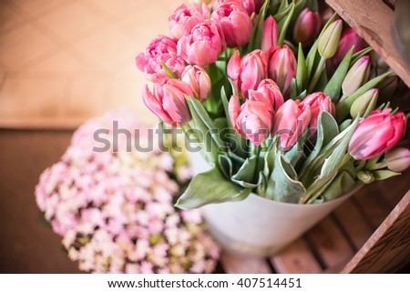 Bunch of magenta pink tulips (Tulipa gesneriana) on wood, hortensia flower and tiled ground background - a decoration in front of flower shop - rustic look - Happy Mothers day or Valentine Card - stock photo