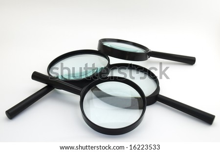 Bunch of magnifiers on a clear background. - stock photo