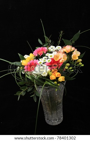Bunch of many different flowers in crystal cut vase on black background - stock photo