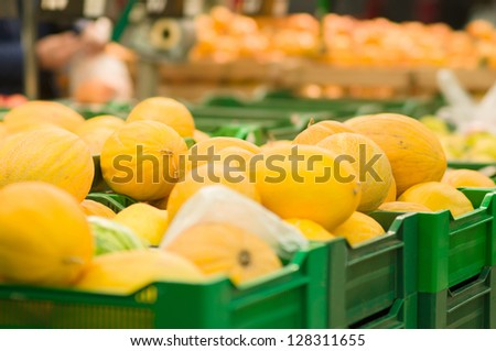 Bunch of melons on boxes in supermarket - stock photo