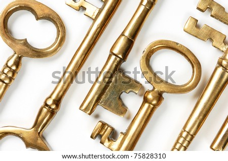 Bunch of old brass keys on white close-up Conceptual abstract background texture - stock photo