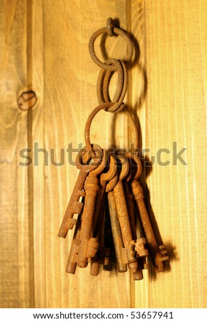 bunch of old rusty keys hanging on a wooden wall - stock photo