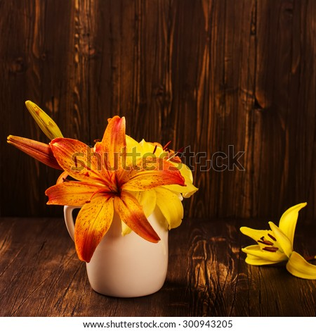 Bunch of orange and yellow lilly flowers on vintage wooden dark table. Space for text. Greeting card. Selective focus. Square image