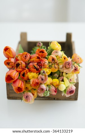 bunch of orange ranunculus and tulips in a vintage box - stock photo