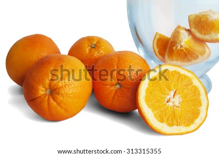 Bunch of oranges with carafe filled with slices of oranges isolated on white background.