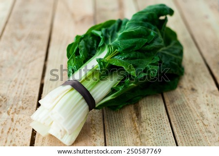 bunch of organic chard on a wooden table - stock photo