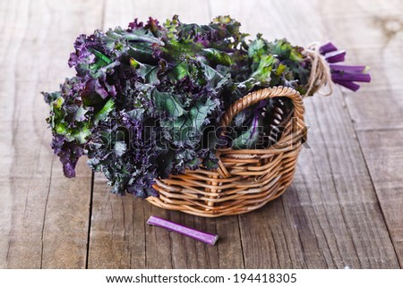 Bunch of organic kale in a woven basket on a rustic wooden background. Selective focus, shallow dof - stock photo