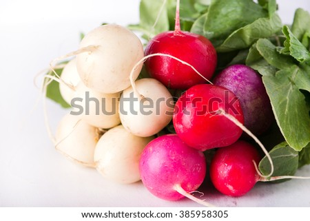 bunch of organically grown, freshly harvested, colorful Easter egg radishes, isolated over white board, close up, horizontal - stock photo