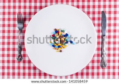 Bunch of pills on the white plate - stock photo