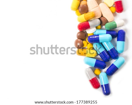 Bunch of pills on white background with blank space for text on left side - stock photo