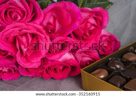 Bunch of Pink Roses on Grey Tulle Fabric and a Box of Gourmet Chocolates - stock photo