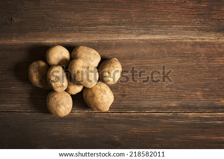 Bunch of potatoes on wooden background close up shoot - stock photo