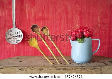 bunch of radish in a blue mug,kitchen utensils - stock photo