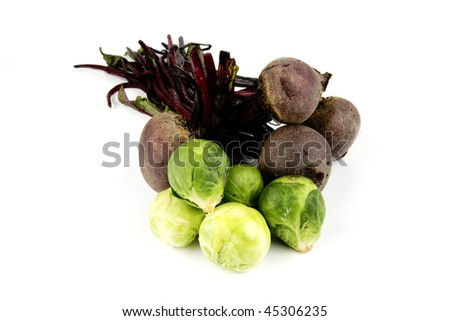 Bunch of raw red beetroot with a pile of small green sprouts on a reflective white background - stock photo
