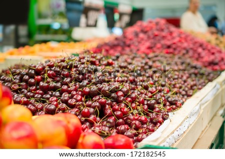Bunch of red cherry on boxes in supermarket - stock photo