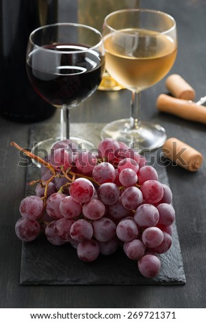 bunch of red grapes and wine glasses on a dark background, vertical - stock photo