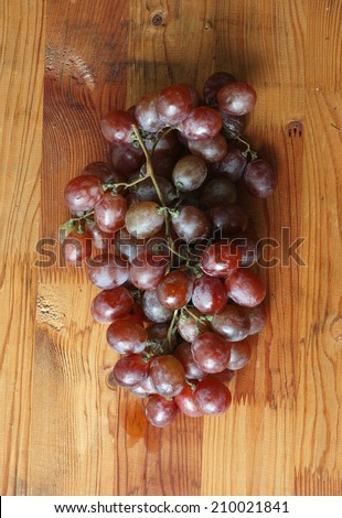 Bunch of red grapes fruit on wood background