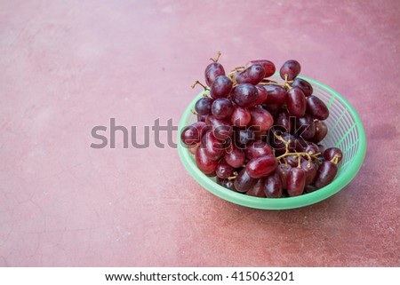 Bunch of red grapes in green basket on a red background. Cluster of grapes. Bunch of grapes. Custer grapes. Bunch grapes. Grapes. Grape.copy space.