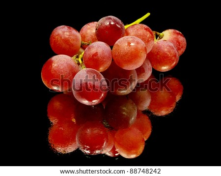 bunch of red grapes on a black background with water drops - stock photo