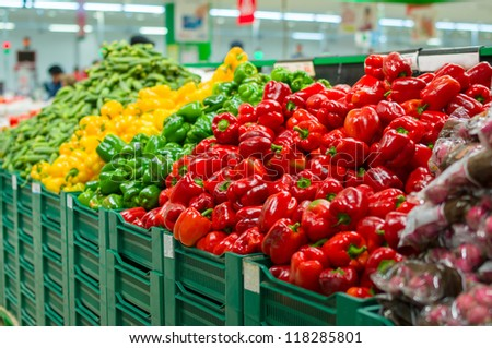 Bunch of red, green and yellow paprika pepper and raddish on boxes in supermarket - stock photo