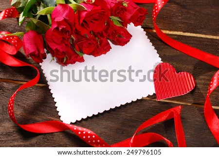 bunch of red roses and blank card for writting text on wooden background  - stock photo
