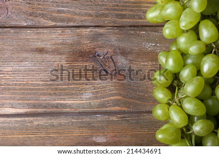 Bunch of ripe grapes on brown wooden background