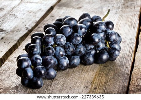 Bunch of ripe juicy blue grapes on a wooden background