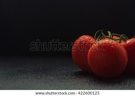 bunch of ripe tomatoes on a dark marble background, water drops on red delicious tomatoes, the freshness and beauty of the advertising. dark textured background - stock photo