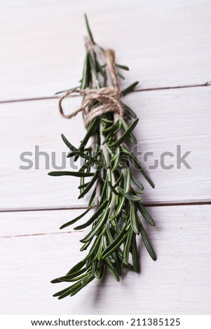 Bunch of rosemary on a rustic wood  - stock photo