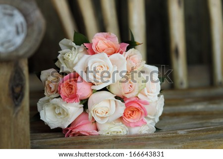 bunch of roses in pink and cream on wooden bench - stock photo