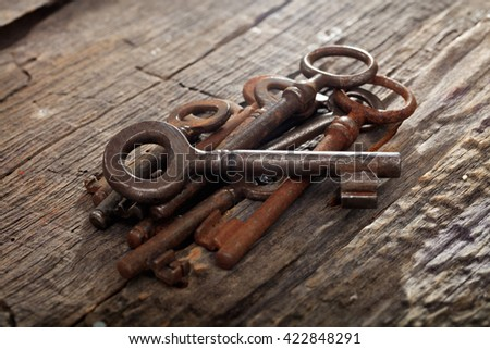 Bunch of rusty old keys on wooden surface