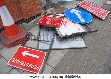 bunch of rusty old road signs at the sidewalk - stock photo