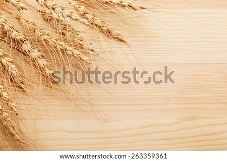 bunch of rye ears on wooden background - stock photo