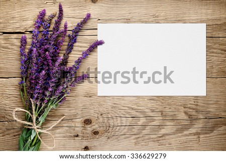 Bunch of salvia and blank greeting card on wooden background - stock photo