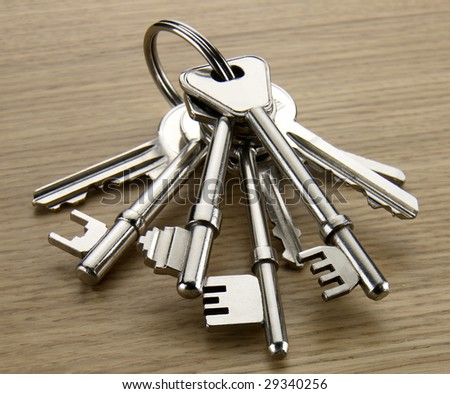 Bunch of silver coloured keys on a wood table - stock photo