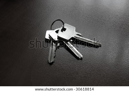 Bunch of silver coloured keys on dark office table - stock photo