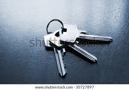 Bunch of silver coloured keys on dark table - stock photo