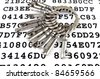 Bunch of silver keys on a sheet with encrypted data - stock photo