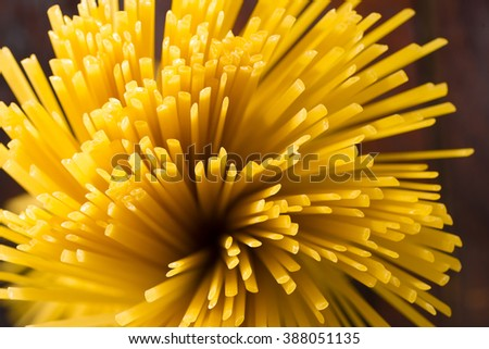 Bunch of spaghetti isolated on dark wood table - stock photo