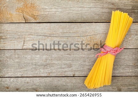 Bunch of spaghetti on wooden table background with copy space - stock photo